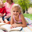 Foto Stock: Close-up of a little girl reading at a picnic