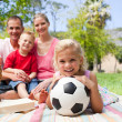 Little blond girl holding a soccer ball at a picnic — Stock Photo
