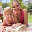 Happy mother and her daughter reading in a park — Stock Photo