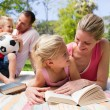 Mother and her daughter reading at a picnic with their family - Stock Photo