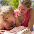 Stock Photo: Portrait of a smiling mother and her daughter reading at a picni
