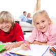 Lively siblings drawing lying on the floor — Foto Stock