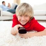 Jolly boy watching TV lying on the floor — Stock Photo