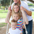 Stock Photo: Happy family swinging