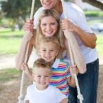 Happy family swinging — Stock Photo #10294447