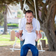 Royalty-Free Stock Photo: Happy father pushing his son on a swing
