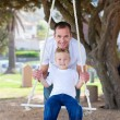 Happy father pushing his son on a swing — Stock Photo