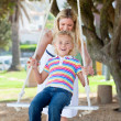 Jolly mother pushing her daughter on a swing — Stock Photo