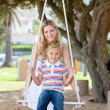 Stock Photo: Caring mother pushing her daughter on swing