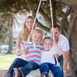 Joyful parents pushing their children on a swing - Stock Photo