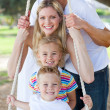 Jolly family swinging — Stock Photo