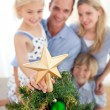 Father lifting his daughter to put the Christmas star on top of - Stock Photo