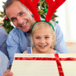 Portrait of a smiling father and his daughter opening Christmas — Stock Photo
