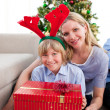 Portrait of a mother and her son holding Christmas gift — Stock Photo
