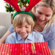 Stock Photo: Smiling mother and her son opening Christmas present