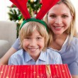 Happy mother and her son unpacking Christmas gift - Stockfoto