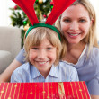 Happy mother and her son unpacking Christmas gift — Stock Photo