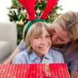 Loving mother kisses son at Christmas — Stock Photo
