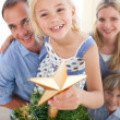 Stock Photo: Father lifting his daughter to put the Christmas star on top of