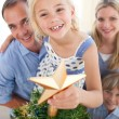 Father lifting his daughter to put the Christmas star on top of — Stock Photo