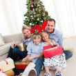 Portrait of a smiling family holding Christmas presents — Stock Photo