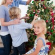 Family hanging decorations on a Christmas tree — Stock Photo #10294472