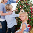 Family hanging decorations on a Christmas tree — Stock Photo