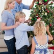 Happy Family hanging decorations on a Christmas tree — Stock Photo #10294473