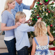 Happy Family hanging decorations on a Christmas tree — Stock Photo