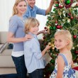 Smiling family decorating a Christmas tree — Stock Photo #10294474
