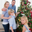Portrait of a young family decorating a Christmas tree - Stock Photo