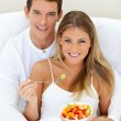 Romaantic couple eating fruit lying on their bed — Stock Photo #10294509