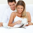 Romantic couple reading a newspaper and drinking coffee — Stock Photo