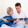 Stock Photo: Smiling little boy playing guitar with his father