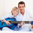 Merry little boy playing guitar with his father — Stock Photo