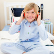 Smiling boy listening music sitting on bed — Stock Photo