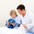Adorable little boy playing guitar with his father — Stock Photo #10294578