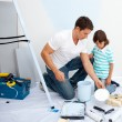 Stock Photo: Father and his son painting in their new house