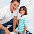 Happy Father and his son painting in their new house - Stock Photo