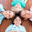 Smiling family lying in circle on the floor — Stock Photo #10294631