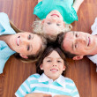 Smiling family lying in circle on the floor — Stock Photo