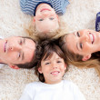 Cheerful family lying in circle on wall-to-wall carpet — Stock Photo #10294637