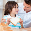 Adorable little boy and his father eating bread — Stock Photo