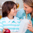 Stock Photo: Joyful little boy and his mother preparing his snack