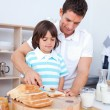 Charming father and his son spreading jam on bread — Stock Photo