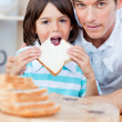 Cute little boy and his father eating bread — Stock Photo