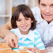 Portrait of a father and his son spreading jam on bread — Stock Photo