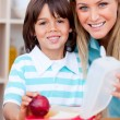 Stock Photo: Cheerful little boy and his mother preparing his snack
