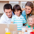 Jolly family using laptop during the breakfast — Stock Photo