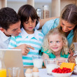 Merry family using laptop during the breakfast — Stock Photo